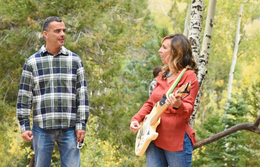 Man and a woman playing guitar in a forest
